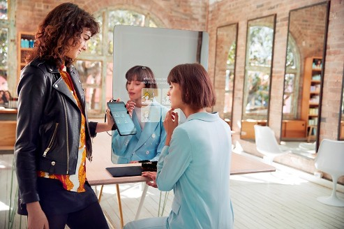 A hairdresser using the Piiq Diigtal smart mirror with a client in a behind the scenes look at funding a tech startup
