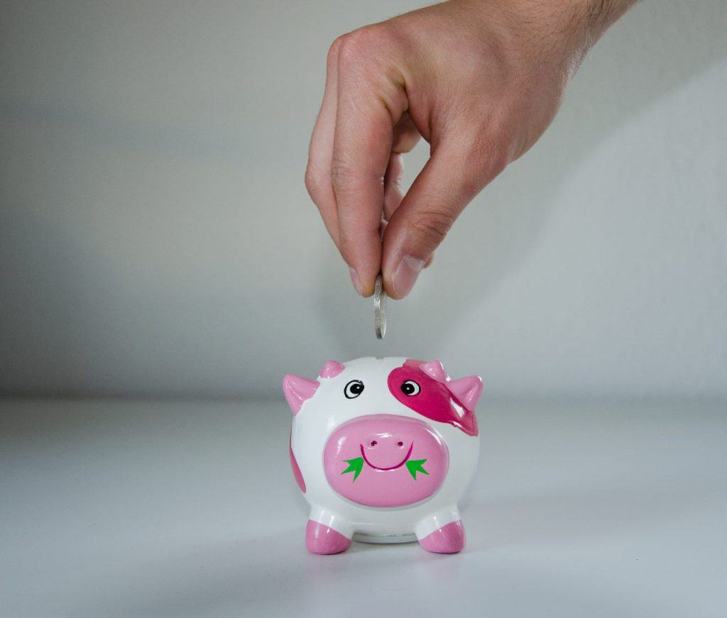 A hand putting money into a piggy bank disproving the financial myth that your business can't save money
