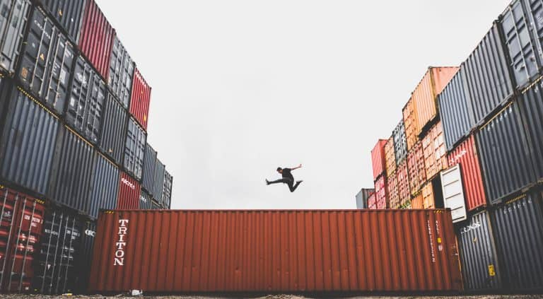 A person jumping across a shipping container in a shipping yard